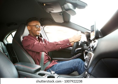 Side portrait of happy young black guy driving car