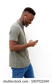Side portrait of happy young black man walking with mobile and earphones against white wall