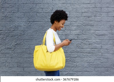 Side portrait of a happy young woman with a bag reading text message on her mobile phone