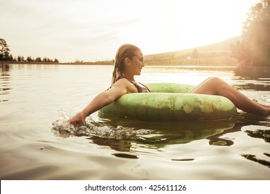 Side portrait of happy young woman in lake on inflatable ring. Young girl relaxing in water on a summer day.