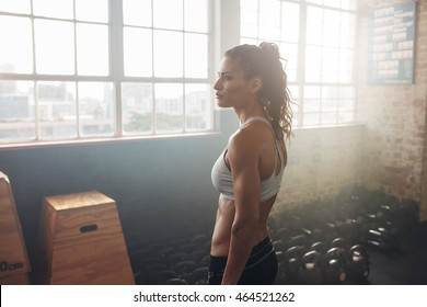Side portrait of healthy crossfit woman relaxing in the gym with kettlebell in background on floor. Focused female athlete at cross fit gym.