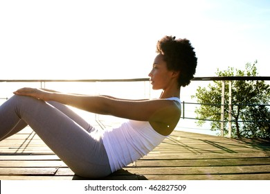 Side portrait of healthy young woman doing stomach crunches near the beach