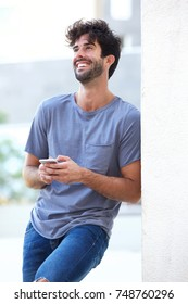 Side portrait of laughing man holding phone leaning on wall outside