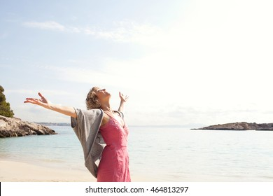 Side portrait of a mature beautiful woman breathing fresh air in a beach destination with blue waters, opening her arms and looking up, aspirational travel lifestyle, outdoors nature.