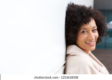 Side portrait of older african american woman smiling by white wall