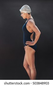 Side portrait of professional female swimmer on black background. Young woman in swimsuit standing with her hands on hips.