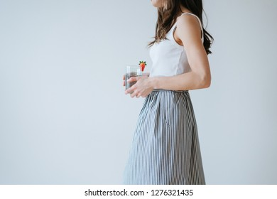 Side portrait of a slim brunette girl in white top and striped skirt against white wall background. She's holding glass of water with fresh strawberry on it. Cropped. No face.