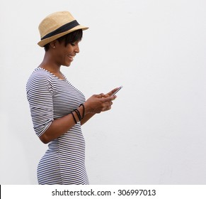 Side portrait of a smiling african american woman walking and reading text message