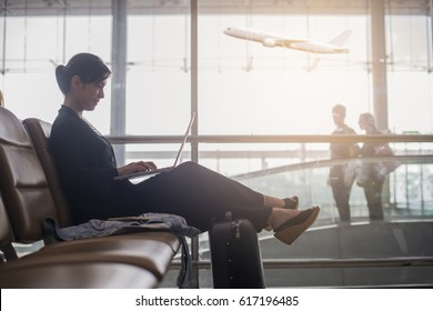 Side portrait of smiling asian businesswoman sitting with laptop, mobile phone and luggage at airport.