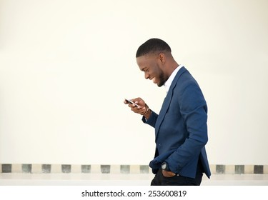 Side portrait of a smiling businessman walking and sending text message on mobile phone