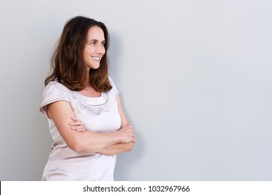 Side portrait of smiling older woman leaning against white wall