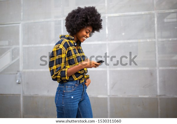 Side portrait of smiling young black woman with afro walking and looking at cellphone
