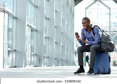 Side portrait of smiling young businessman sitting on suitcase looking at phone