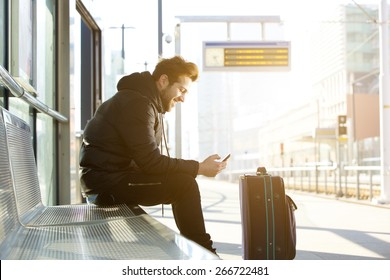 Side portrait of a smiling young man sitting with mobile phone and bag waiting for train