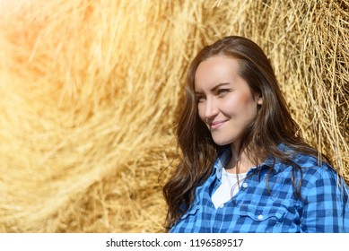 Side portrait of smiling young woman standing leaning on haystack in blue caged man's shirt