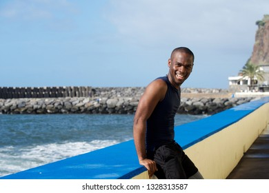 Side portrait of sporty african american  man leaning against wall by sea