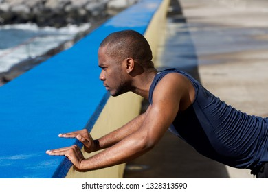 Side portrait of sporty african american  man leaning against wall