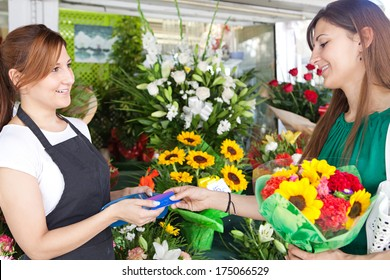 Side portrait view of an attractive shopper woman customer buying and paying with a credit card at a small florist business store and the shop attentant taking payment from credit card, outdoors.