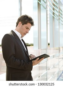 Side portrait view of a smart senior businessman using a technology tablet while leaning on a glass modern architecture office building in the city.