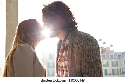 Side portrait view of a young romantic couple kissing while on vacation in a destination city, with the sun rays filtering through their lips.