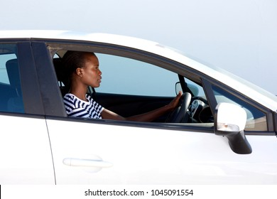 Side portrait of young african woman driving car