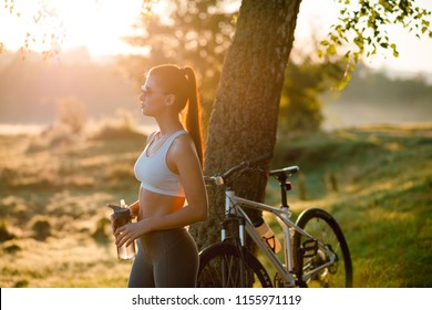 Side portrait of young attractive bruntte woman in sportswear drinking water from the bottle after bycicle ride. Park. Sunny summer day