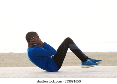 Side portrait of a young black man exercising on the beach doing sit ups