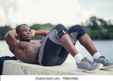 Side portrait of a young black man doing sit ups