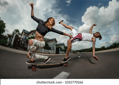 Side portrait of young couple skateboarding together on road. Young man falling down and woman getting hold of him on longboard