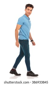 side portrait of young man in blue shirt walking in isolated studio background, looking at the camera