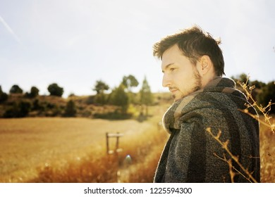 Side portrait of a young man enjoying in calm the morning autumn sun in a path of a yellow field with the backlight from the blue sky