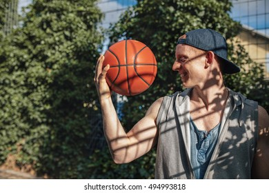 Side portrait of young man looking at basketball in hand. Teenage guy holding a ball on outdoor court.