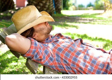 Side portrait of young man lying on hammock resting with cowboy hat