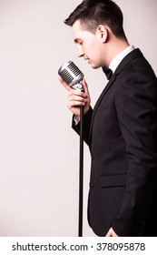 Side portrait of young man in suit singing with the microphone. Isolated on grey background. Singer concept.