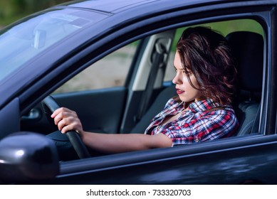Side portrait of young woman driving a car on high speed