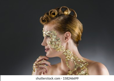 Side portrait of a young woman with an elegant gold leaf make-up and hair styling with an exclusive screwed curls.