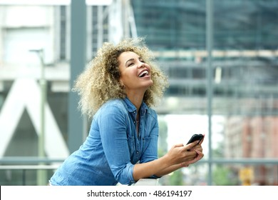 Side portrait of young woman laughing with smart phone