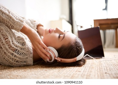 Side portrait of young woman sleeping with headphones