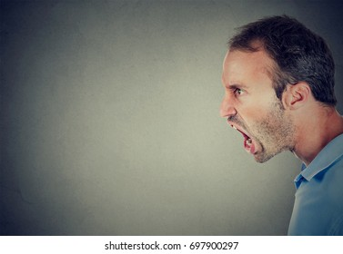 Side profile of an angry man screaming