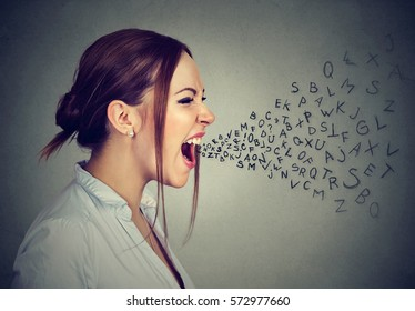 Side profile angry woman screaming with alphabet letters flying out of wide open mouth isolated on gray wall background
