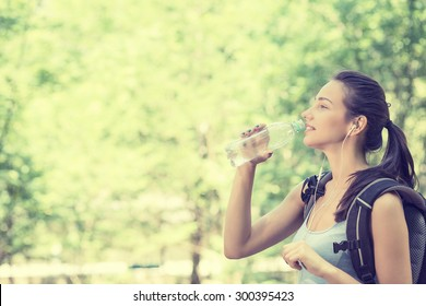 Side profile attractive happy young woman hiker with backpack drinking bottled water walking on a country forest trail landscape on a summer hot day