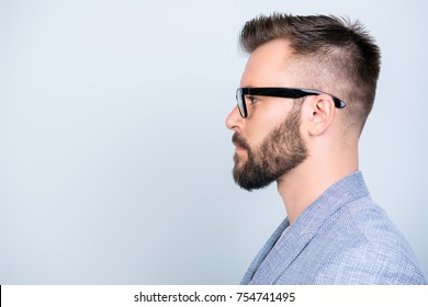 Side profile close up photo of successful young serious handsome brunet bearded businessman in formal outfit and black glasses on pure blue background