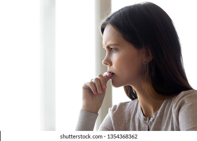 Side profile close up view face of serious pensive young woman thinking about problem difficulties biting nail finger, feels nervous frustrated puzzled, hard make decision stressful situation concept