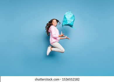 Side profile full length body size photo of cheerful pink positive preteen schoolchild catching her backpack wearing pants trousers footwear isolated pastel blue color background