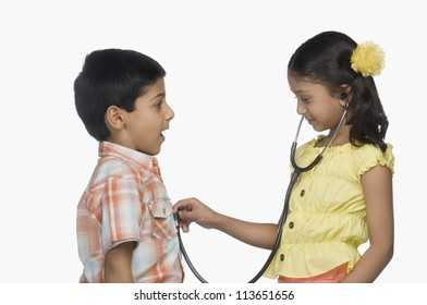 Side profile of a girl examining a boy with a stethoscope