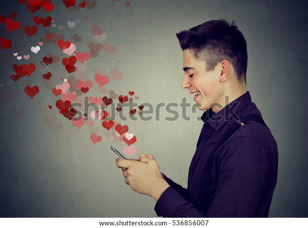 Side profile happy man sending love sms text message on mobile phone with red hearts flying away from screen isolated on gray wall background. Positive human emotions