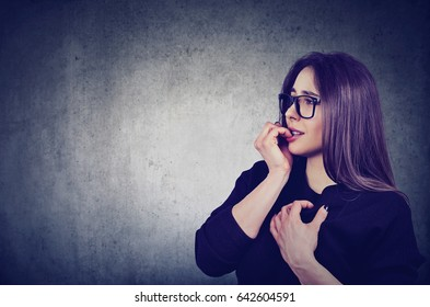 Side profile hesitant anxious woman biting her fingernails looking sideway isolated on gray wall background. Negative human emotion