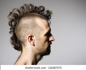 Side profile of man with half shaved hair and beard