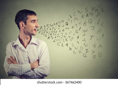Side profile man talking with alphabet letters coming out of his mouth. Communication, information, intelligence concept