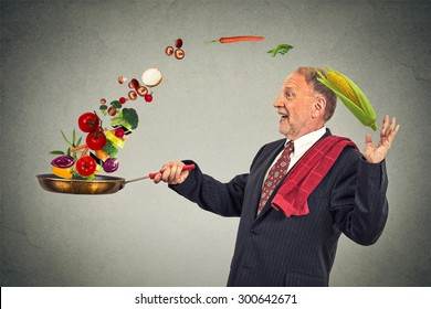Side profile mature happy businessman cooking vegetables with a pan isolated on grey wall background. Positive face expression emotion.